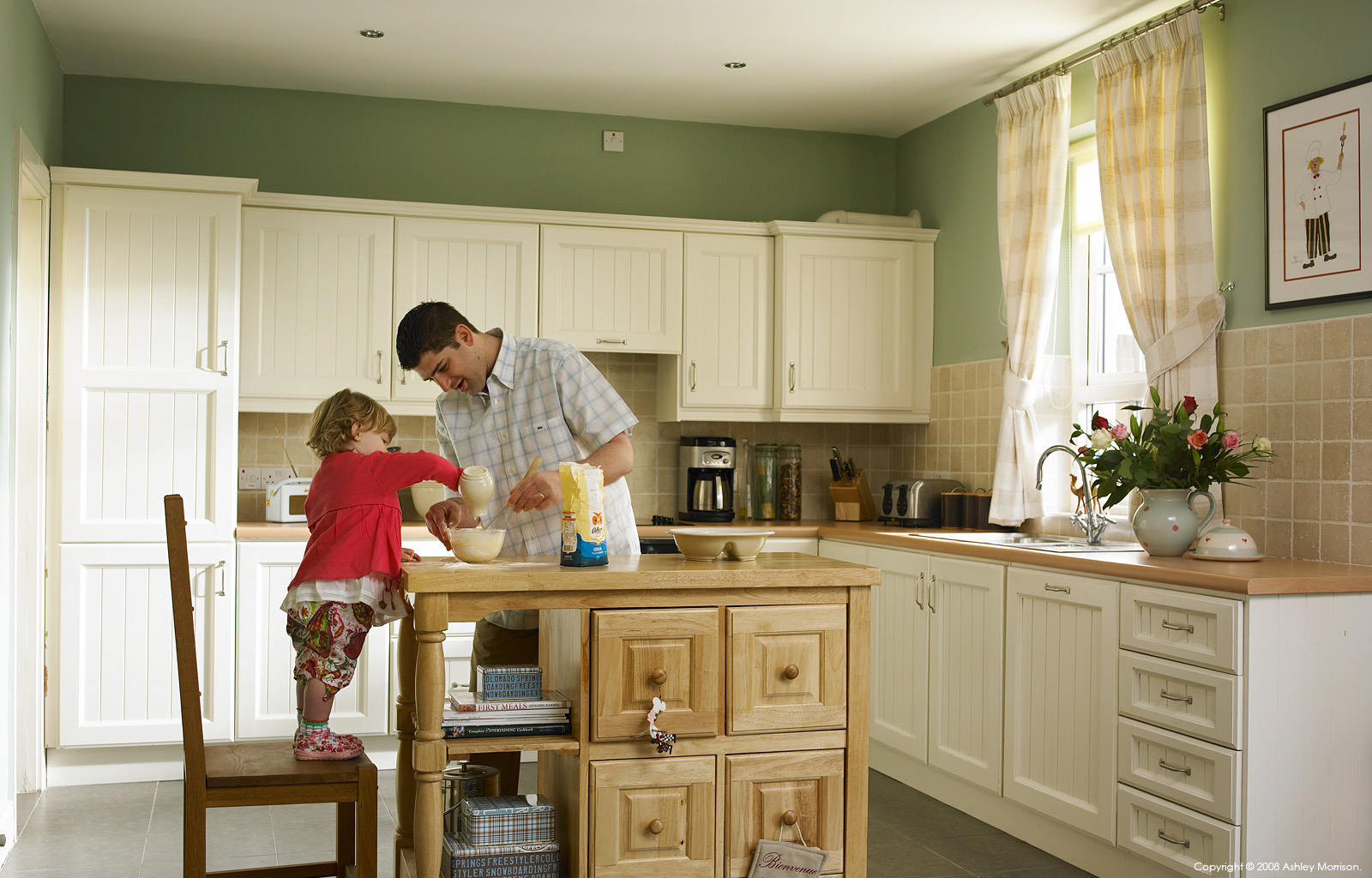 Matt King with his daughter in the kitchen of their home on the grounds of Castle Leslie in County Monaghan by Ashley Morrison.