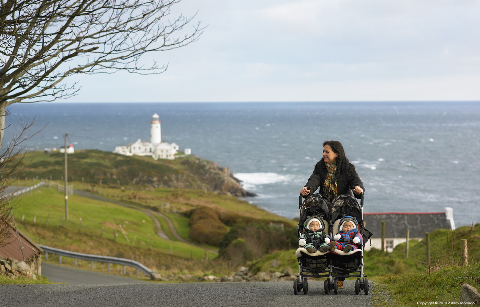 Sarah Mitchell with her twins walking outside her cottage called 'Paddy Mors' near Fanad Head in County Donegal.