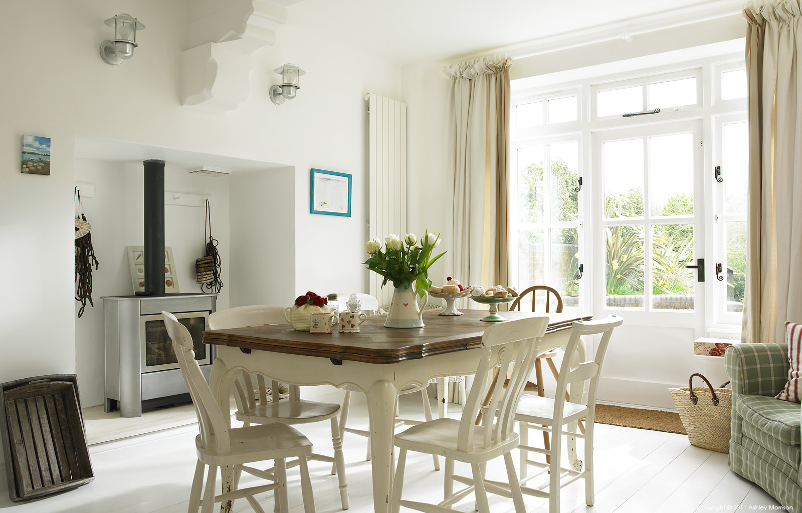 The kitchen table in Beth and Jason Cooper's three-storey period terrace called 'Brick Rose House' in the West Sussex village of West Wittering.