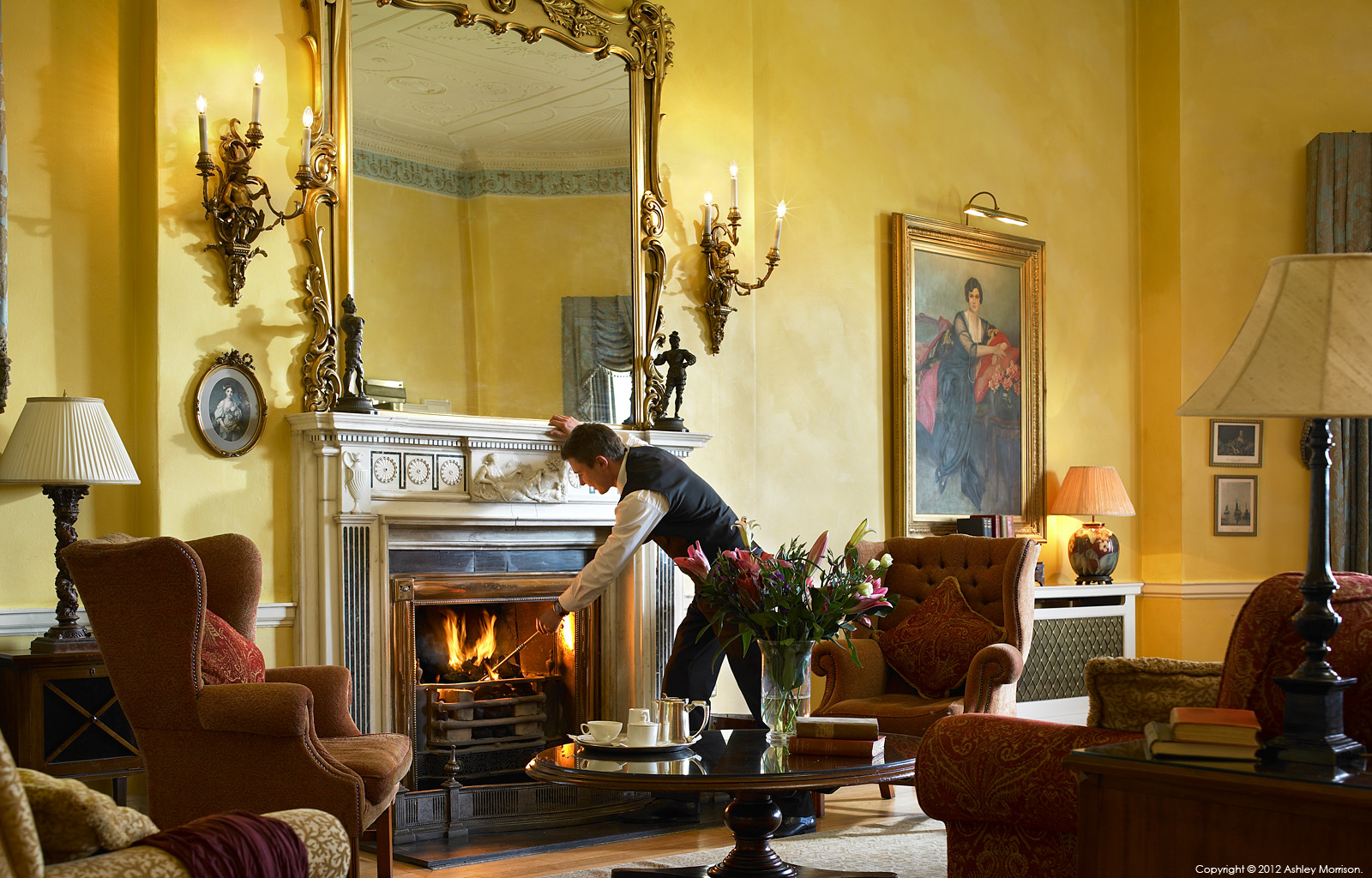 A member of staff stoking the fire in the Reading room in Mount Juliet House on the Mount Juliet Country Estate in County Kilkenny by Ashley Morrison.